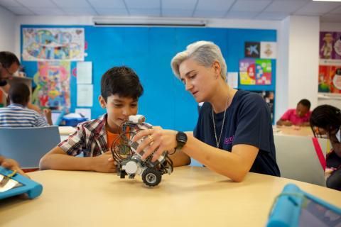 Monitora y niño montando un robot